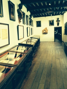 A room with cases and prints showing the work product through history of known printers in Antwerp.
