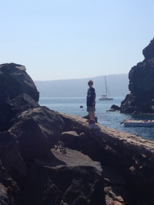 Walking a narrow sea wall to get to St. Nicholas Church on the rocks off of Ammoudi.